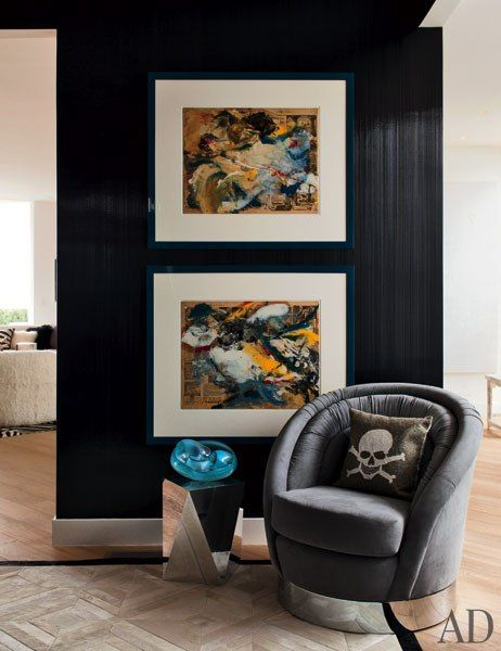 Elton John and David Furnish's Beverly Hills Home designed by Martyn Lawrence Bullard. Two Willem de Kooning works on paper hang next to a Bullard-designed chair and a Ligne Roset side table in the dining room.