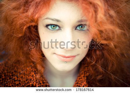 young beautiful red curly hair woman at the park by Eugenio Marongiu, via Shutterstock