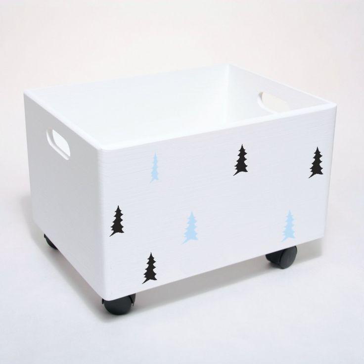 Drewniana skrzynia na zabawki w kolorze białym udekorowana skandynawskim motywem. Może dodatkowo posiadać kółka. Przechowywanie w pokoju dziecka.