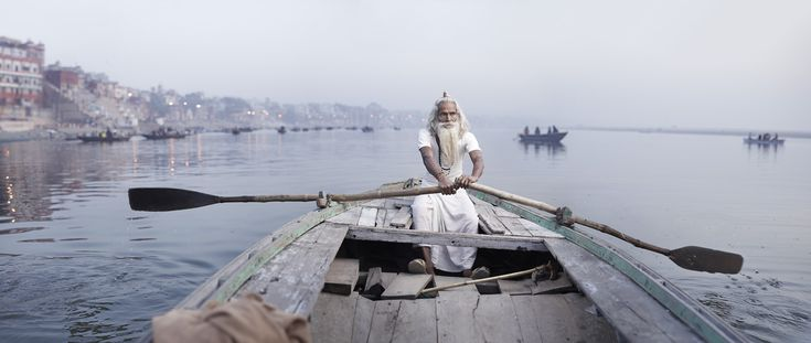 Ascetic priest Baba Vijay Nund rows a boat along the Ganges River. Varanasi, India