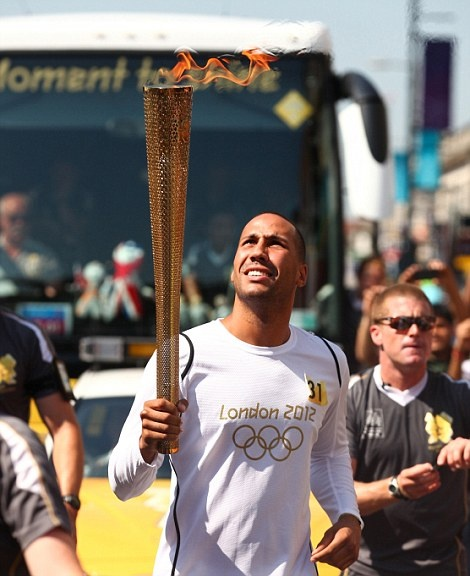 Boxer and 2008 Olympic gold medallist James DeGale runs with the flame on Day 68 of the torch relay