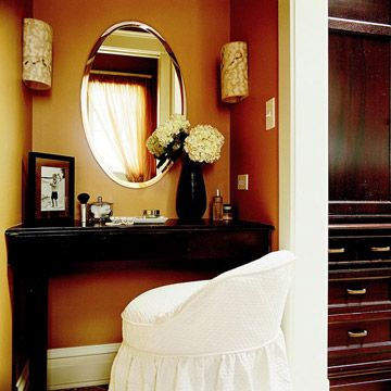 Sophisticated built-in vanity table in a caramel painted nook with oval mirror and wall sconces #vanity #mirror #scones