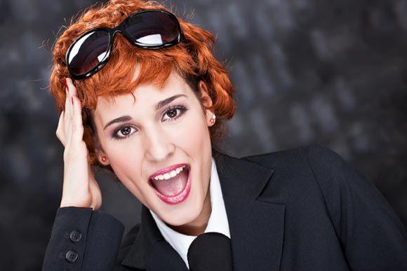 Junge Businessfrau im Anzug trägt große Sonnenbrille im roten Haar