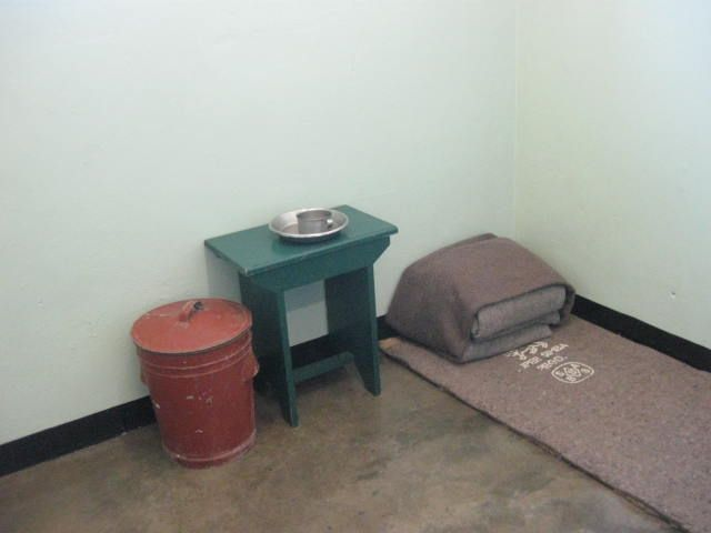 Nelson Mandela's cell. While he was there it was more 'furnished' with a small table to use as a desk, books, photos, and a simple bed etc.