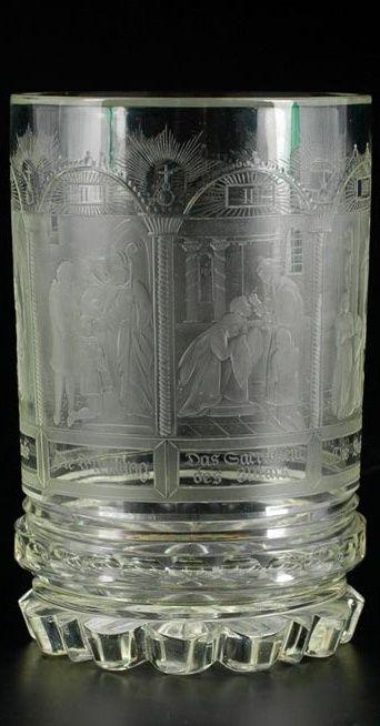 """Číše s vyobrazením Sedmi svátostí. Čechy, Jablonec nad Nisou, řezal Anton Simm, kolem 1830. Silnostěnná válcovitá číše z broušená čiré skloviny s laločnatým okrajem a radiálně uspořádanými řezy na spodní straně, plášť s náročně řezaným religiózním námětem sedmi křesťanských svátostí, v obloukovitých arkádách jsou provedeny řezby ilustrující jednotlivá znamení zprostředkující boží milost s příslušným textem, signováno v sedmém poli vpravo dole """"AS"""". Stav A, v. 16,2 cm. Anton Simm, významný…"""