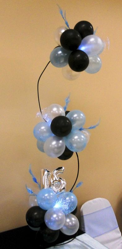 Curved balloon topiary centerpiece with feathe accents and fiber optic lights!