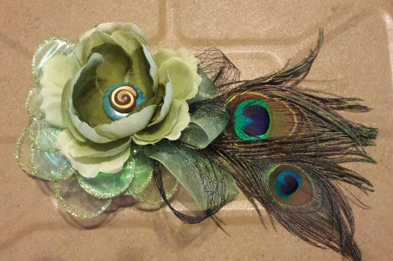Green peacock fascinator with gold and turquoise accents. Measures 9 by 5 and is mounted on a 3.5 by 2 plastic haircomb.