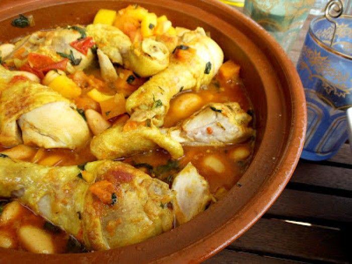 Afrikaanse kip tajine   6 kipdrumsticks  ½ gele paprika  1 ui  200 g pompoen  1 blik boter(lima)bonen (240 g uitlekgewicht)    (ev vervangen door witte bonen)  2 tomaten  2 cm verse gemberwortel  2 el verse majoraan  1 tl kaneel  2 tl raz el hanout (Marokkaans specerijenmengsel)  zout  4 el olijfolie