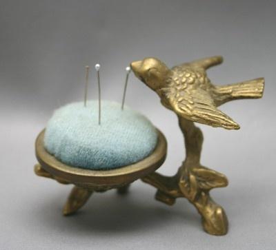 Vintage cast brass Blue Bird on branch with nest pin cushion. Photo via ebay