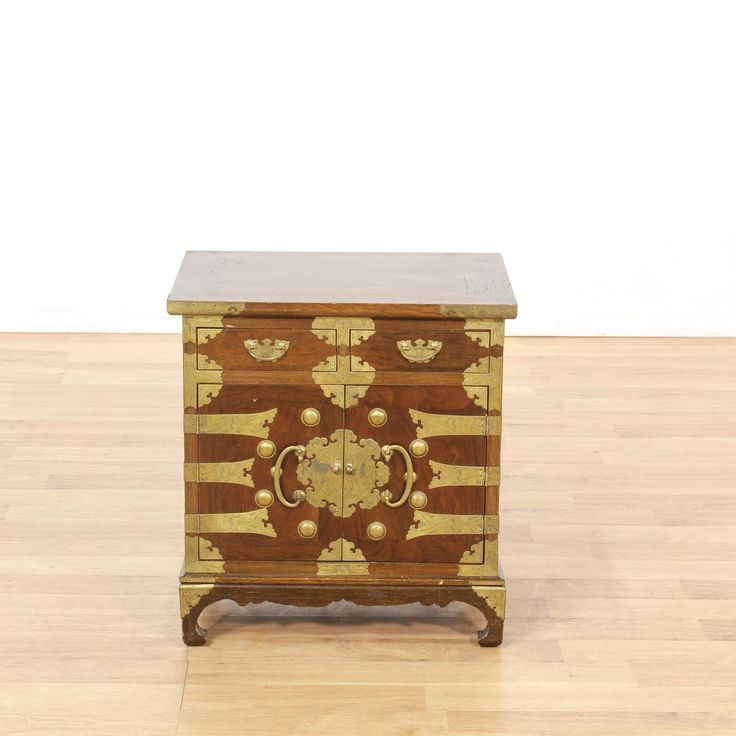 This Chinese nightstand is featured in a solid wood with a warm walnut finish. This end table has shiny ornate brass mounted hardware, a large interior cabinet with 2 drawers and curved base trim. Eye catching side table with lots of storage! #asian #dressers #nightstand #sandiegovintage #vintagefurniture