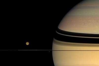 A view of Saturn, the shadow of the rings, and the moon Titan