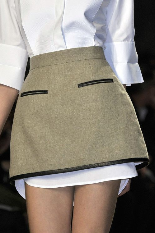 Leather-edged tailored skirt layered over a crisp white shirt; chic structured fashion details // Céline
