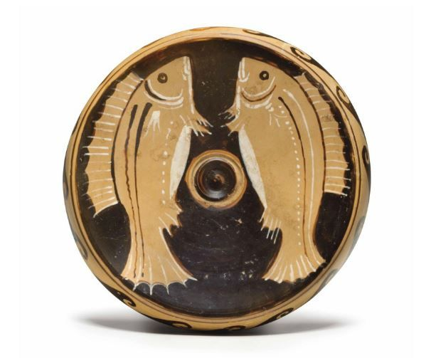 Fish plate, red-figured, Campania, attribuited to the Elliott painter, 350-325 B.C.  With two wrasse, a band of wave on the overhanging rim, details in added White, 16.8 cm diameter. Private collection