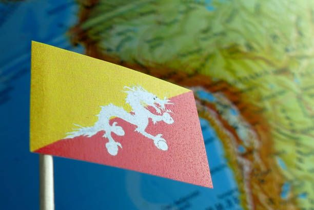 bhutan flag with a globe map as a background macro