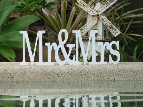 WHITE Mr&Mrs ARE CURRENTLY IN STOCK AND AVAILABLE FOR NEXT DAY DISPATCH.  Make your own unique table decorations and centrepieces with my stunning wooden wedding words. White is the most popular choice for wedding signs, however feel free to contact me if you would like another colour. If you like a little bling I have silver and white glitter that will add the perfect sparkle to your wooden wedding name.   * Mr&Mrs wooden wedding sign in Century font  * Choose either 15cm x 18cm high...