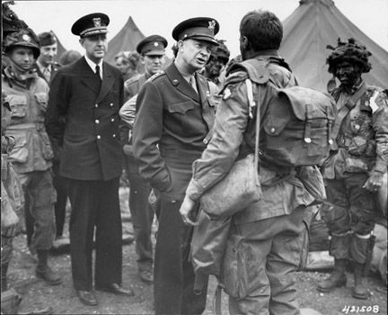 General Eisenhower speaks with paratroopers of the 101st Airborne Division just before they board their planes to participate in the first assault of the Normandy invasion, 6/6/44