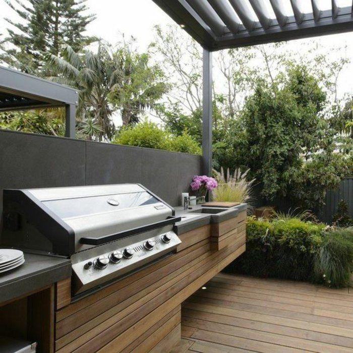 cuisine d'été aménagée sous une pergola, construction moderne en bois et béton