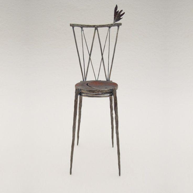 鉄で出来ている椅子のオブジェ。スタイリッシュなハイバックデザイン。卓上サイズながら繊細に作りこまれたディテール。トップに小さな翼が付いています。正面からの写真。