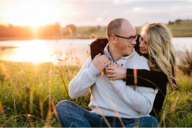 couple sitting in grass in sunset