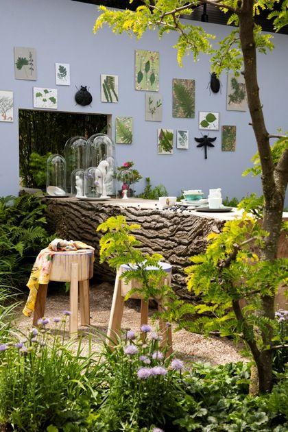 Massieve boomstamtafel en decoratieve tuinmuur.