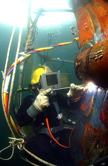 Professional diver using surface supplied diving equipment performing underwater welding