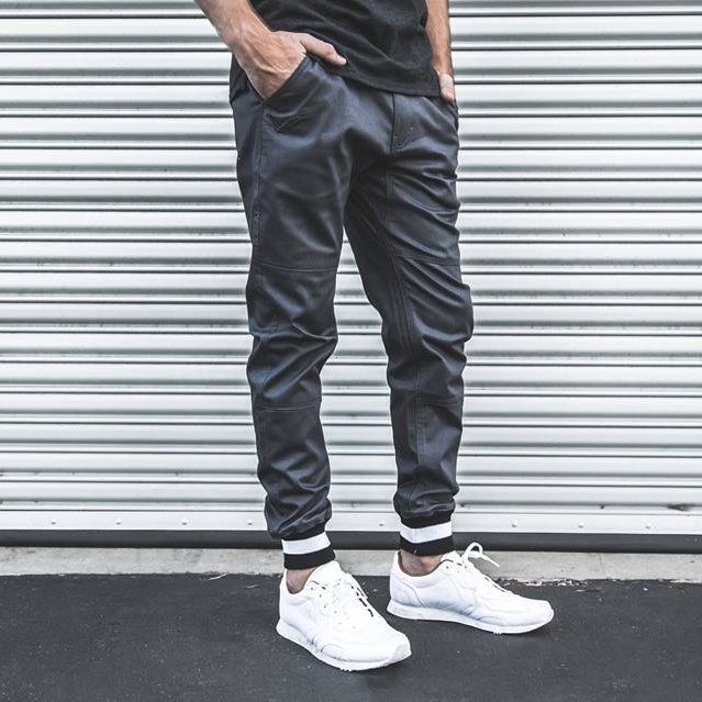 """Publish Brand's signature stretch-twill jogger pants get a varsity-inspired update with stripe-tipped ribbed cuffs. The slouchy, panel-constructed style goes one step further into versatile streetwear with a water-repellent and stain-resistant coating. 30"""" ieam; 9"""" leg opening; 10"""" front rise; 12 1/2"""" back rise (size 32). Zip fly with button closure. Front slant pockets; back welt pockets. D-ring belt-loop detail perfect for keys. 98% cotton, 2% spandex. Mid rise.True to size. Please allow…"""