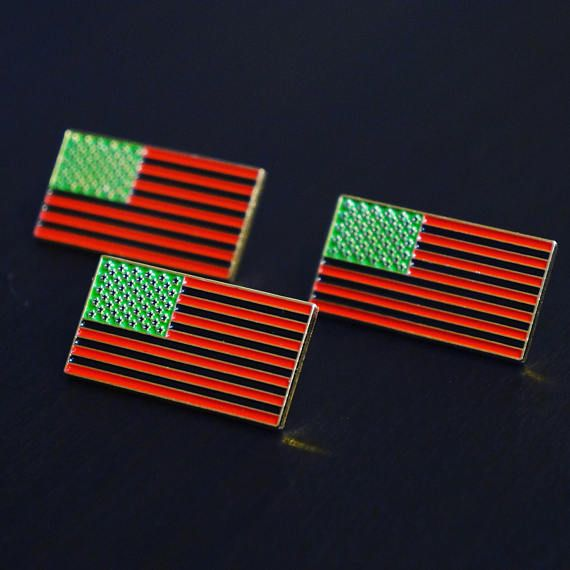 """Celebrate Black History year round with our Red Black and Green American Flag enamel lapel pin. Measures 1.25"""" from corner to corner."""