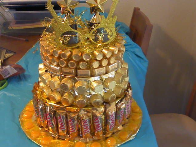 Golden birthday candy cake  empty Christmas cookie tins wrapped in dollar store foil paper with candy hot glued on; base is a piece of cardboard wrapped in foil