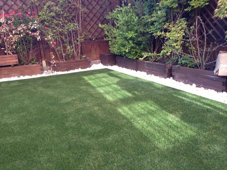Jardin renovado con césped artificial y delimitacion de jardineras con perfiles de aluminio y bolo blanco alrededor, simplemente genial!!!