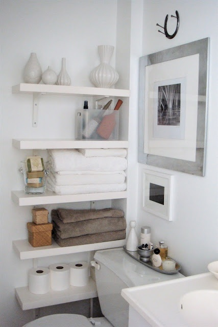 white shelves that match the wall offer storage without cluttering visual space for long narrow small bathroom