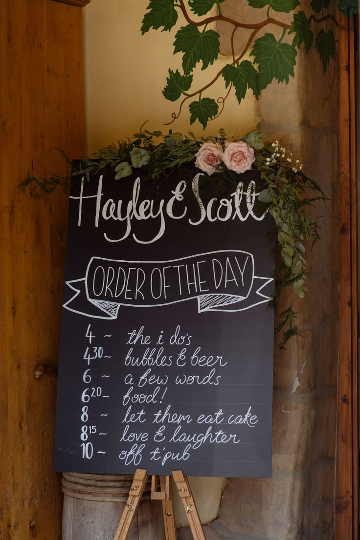 Rustic chalk board with order of the day, pink roses and foliage. rustic wedding decor for a barn ceremony. Wedding ideas.