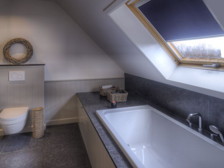 Toilet and bath surround in cottage style, with natural stone. Designed by Dzignstone.