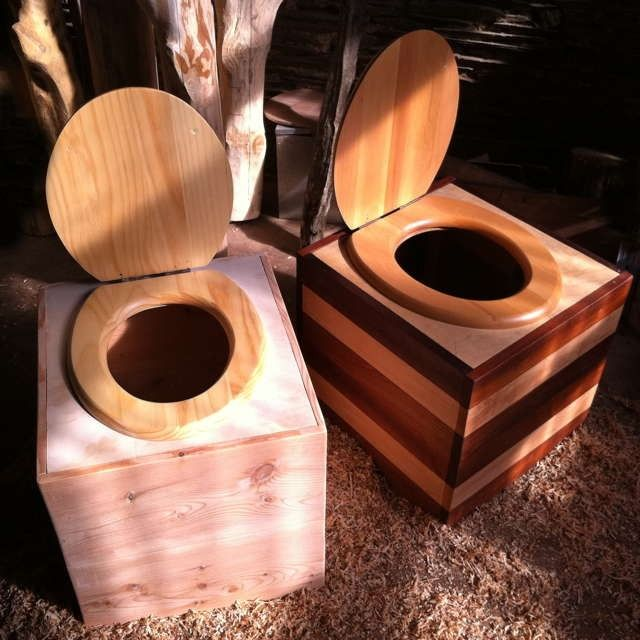 Can you still buy wooden toilet seats?   You could make the top of the box hinge for cleaning. You could tile the whole box.