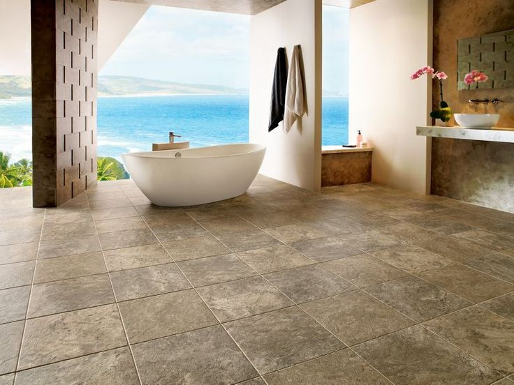 Bathroom with a clear design with a white bathtub on a brown travertine floor with an amazing view to the sea  #travertine #floor #bathroom #interior #naturalstone