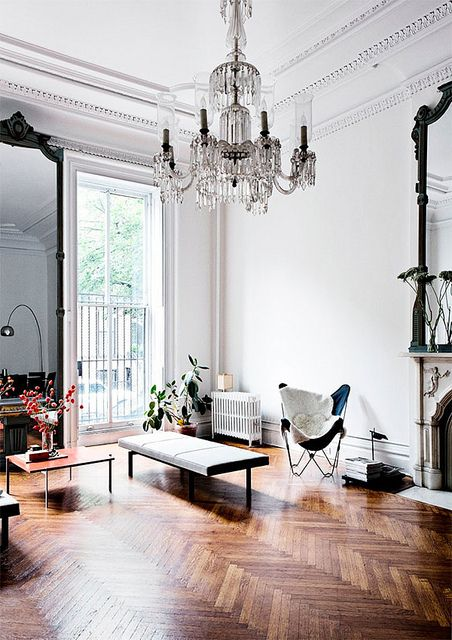 Beautiful wooden floor compliments monochrome scheme in this Period Living Room. Appearance is very contemporary even though a chandelier is in place and mirrors and architectural features are all designs (or based on designs) from an era past.