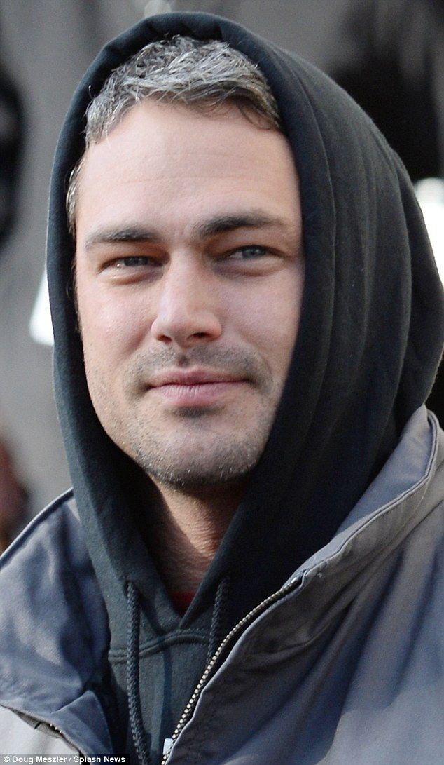 A touch of gray: Taylor's famous gray-tinged hair poked out from under his hood as he watched the parade.