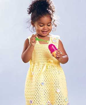 This darling yellow dress has a handful of pastel blossoms sewn randomly to it.