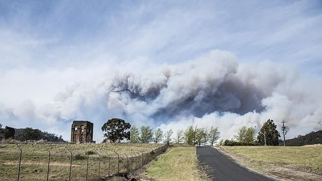 """NSW fires. """"The blast furnace ruins are an awesome piece of old furniture and one of the most photographed items in Lithgow,"""" Rawsthorne said. """"With the sunset, smoke and fire in the background, it looked brilliant."""" (Photo: David Rawsthorne)"""