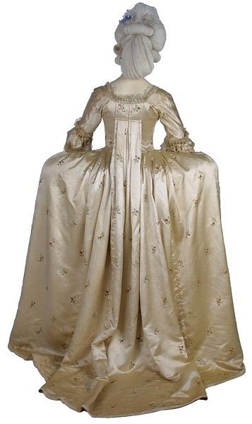 This is an example of the most formal ensemble for a woman in the late 1770s, except for court dress. It is a sack-back gown, worn over square hoops and very elaborately decorated. Feathers, lace, raffia tassels and lengths of satin embellish an already embroidered satin. The pale colors, small floral motifs, and light application of the decorations show that the influence of the Rococo style was beginning to wane.