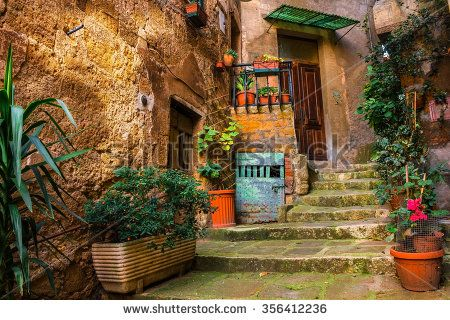 old traditional courtyard in small medieval town of Sorano in Italy with potted plants - stock photo