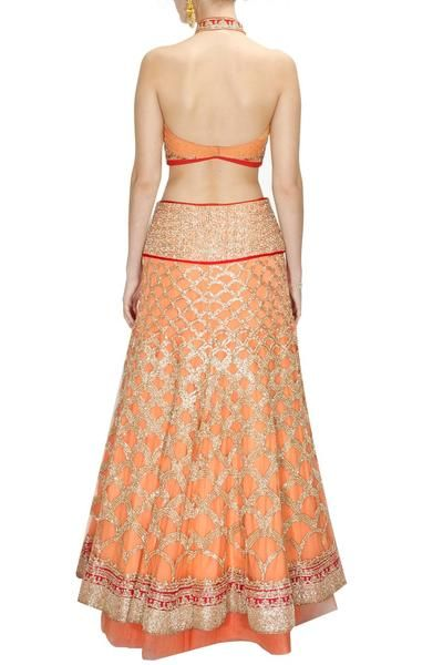 This peach colour lehenga choli is made with zari embroidery all over inspired by fish scales paired with peach halter blouse with net panel and red embroidered mandarin collar. It is styled with peach net dupatta with motifs all over. This bridal lehenga choli comes with an underskirt. This is a well tailored, perfect fit, handcrafted piece of art.