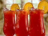 Neelys Hurricane--  Ice cubes  2 ounces light rum  2 ounces dark rum  2 ounces passion fruit juice  2 ounces pineapple juice  1/2 lime, juiced  1 tablespoon grenadine  1 orange, sliced into wheels, for garnish