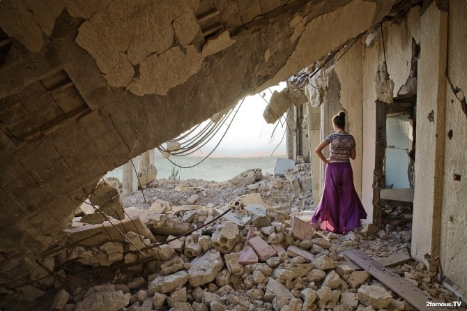 A woman in a bombed house