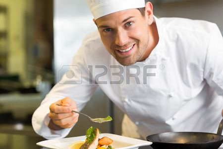 Closeup of a smiling male chef garnishing food in the kitchen