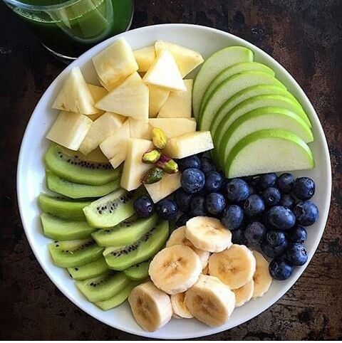 Fruit plate: kiwis, pineapples, green apples, blueberries, bananas, & pistachios.