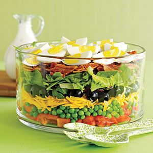 This classic layered salad is always popular at covered dish and potluck suppers with its colorful layers of lettuce, bacon, tomato, olives, green peas, carrot and hard-boiled eggs.
