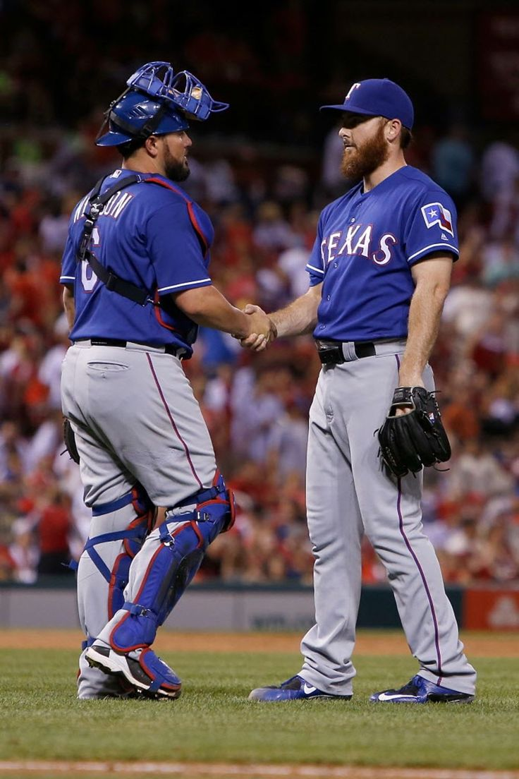 Bryan Holaday #8 congratulates Sam Dyson #47 of the Texas Rangers after the Rangers defeated the St. Louis Cardinals