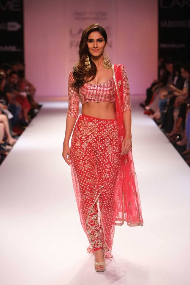Vaani Kapoor in Payal Singhal's Indo-Western fusion ensemble; a cranberry-red blouse, embroidered churidar, sheer, sequined skirt, and dupatta.