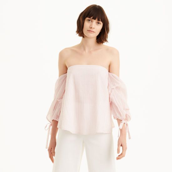 """Rendered in a gauzy cotton, the Liki boasts a fresh off-the-shoulder silhouette and artfully rumpled sleeves for a dose of texture and visual interest. Cut wide and swingy, it feels just as easy as it does feminine. Cotton Relaxed, cropped fit 32&fracc12;"""" in length, based on a size 6 Off-the-shoulder silhouette; straight neckline with elastic band at the back; split sleeves with adjustable self-ties at the cuff; curved hem; placed stitches"""
