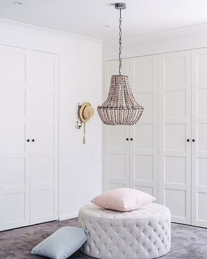 [ THREE BIRDS HOT TIP ] Renovating doesn't have to exy... When @ikea_australia doors and Bunnings handles look a million bucks! wooden chandelier @hamptons_at_home_sydney | ottoman @freedom_australia | pink and grey cushions @adairs | carpet #bunnings